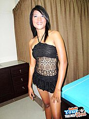 Koy Standing Beside Bed Wearing Black Short Dress Smiling Brightly