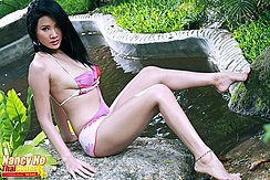 Seated On Rock Wearing Swimsuit Stretching Out Her Legs Long Hair