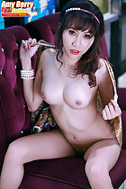 Seated nude on sofa bare breasts legs open