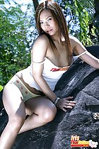 Iris seated on rock wearing white top in panties