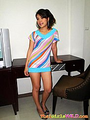 Pepe Standing Beside Desk And Chair Wearing Multi Coloured Short Dress In Heels