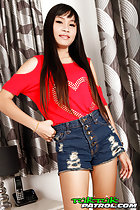 Standing with hand on hip wearing red top in denim shorts